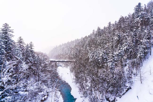 Beautiful outdoor nature landscape with shirahige waterfall and bridge in snow winter season Hokkaido Japan